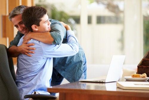 Padre dando un abrazo a su hijo adolescente.