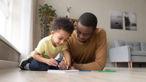 Padre e hijo jugando a juegos usando solo papel y boli.