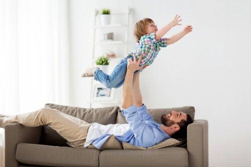 Padre implicado jugando con su hijo en el sofá.