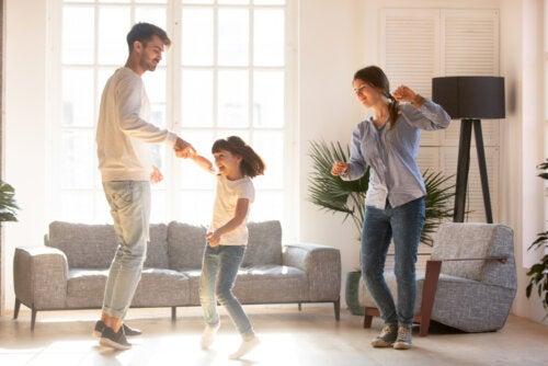Familia bailando en el salón de casa.