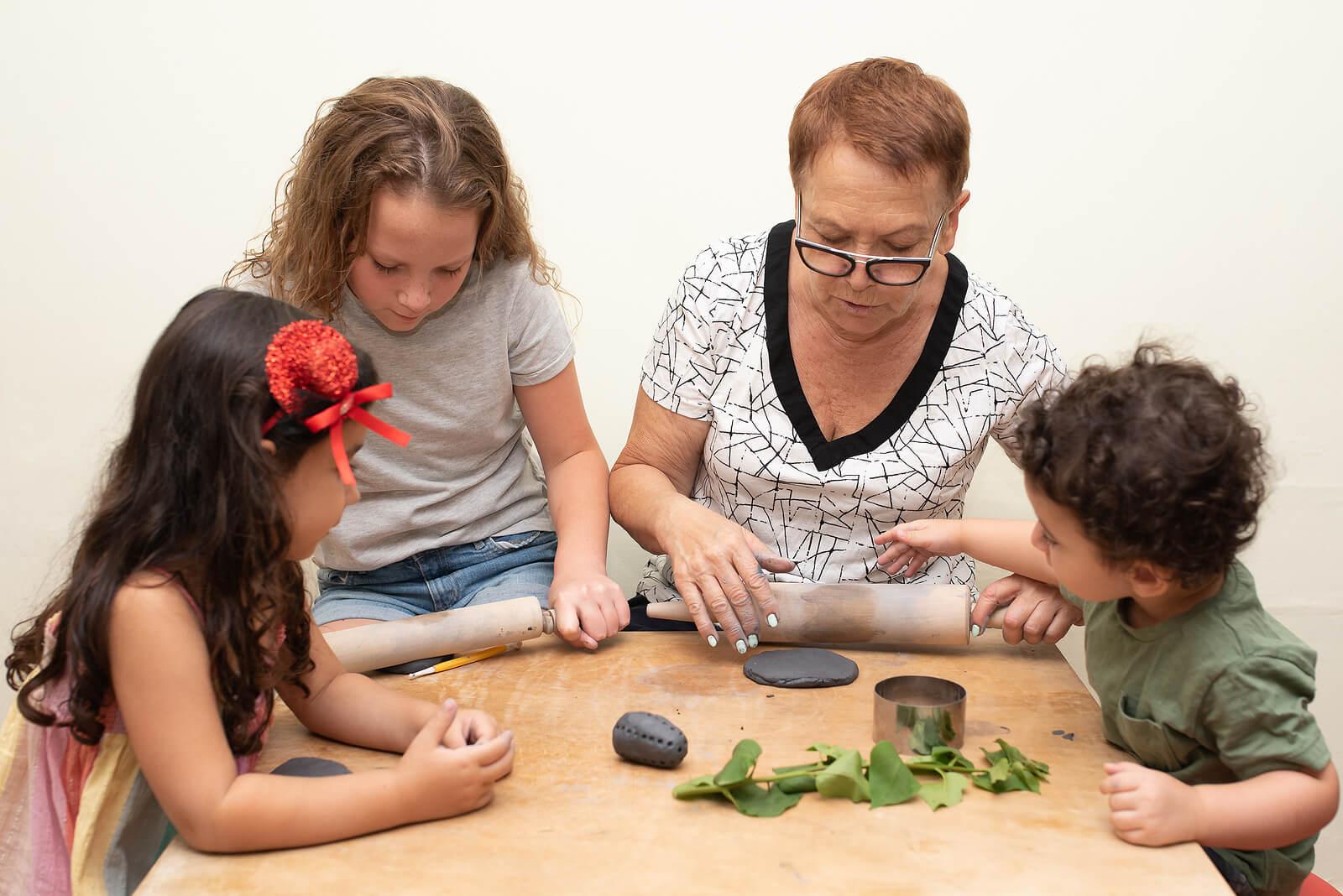 Abuela haciendo figuras de arcilla con sus nietos.