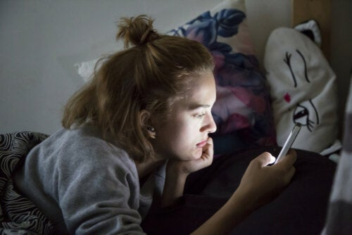 Adolescente consultando sus redes sociales en el móvil.