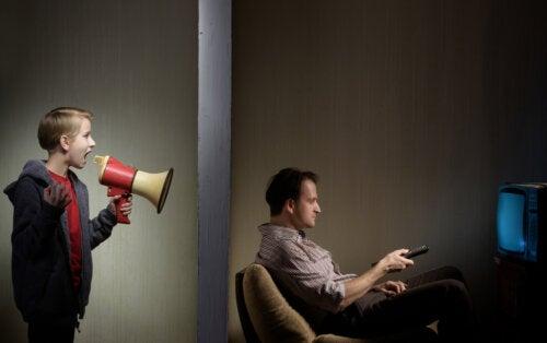Hijo adolescente busca el afecto de su padre, que está viendo la televisión y no le hace caso.