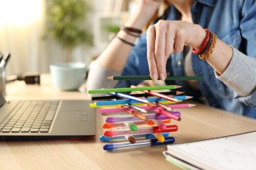 Adolescente aburrida jugando con los lápices de colores y sin hacer sus tareas.