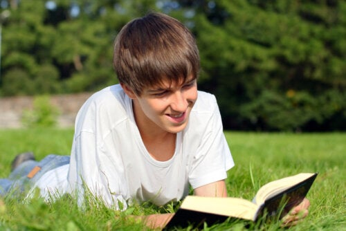 Chico joven leyendo uno de los libros para viajar en el tiempo tumbado en el césped.