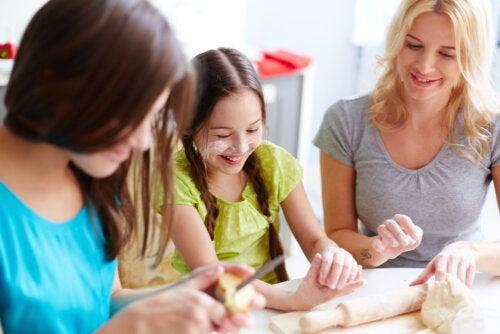 Chicas adolescente haciendo una pizza con su madre.