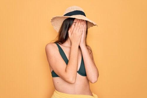 Chica adolescente con traje de baño tapándose la cara porque se avergüenza de su cuerpo.