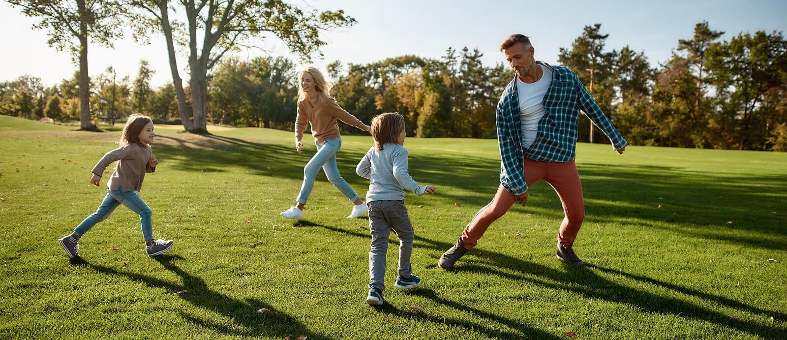 Familia corriendo al aire libre teniendo en cuenta la importancia del juego libre para el desarrollo de sus hijos.