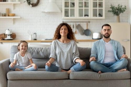 Familia realizando actividades de meditación y mindfulness en el sofá de casa.