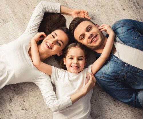Padres tumbados junto a su hija en suelo sonriendo debido a las enseñanzas que les ha proporcionado.