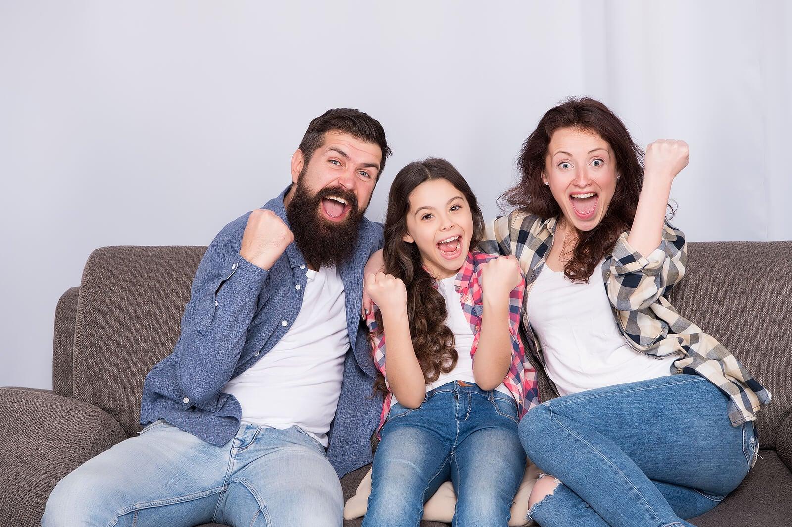 Padres con su hija haciendo actividades para trabajar la competencia lingüística en casa.