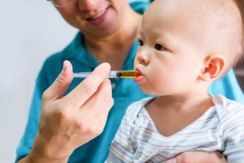 Padre aprendiendo a dar un medicamento a su hijo.