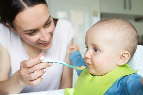 Mamá dando de comer a su bebé y empezando la introducción de alimentos poco a poco.