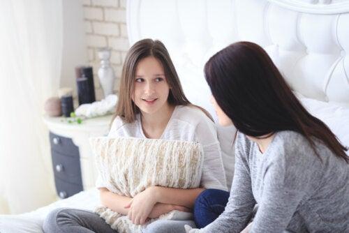 Madre hablando con su hija para evitar conflictos con adolescentes durante la cuarentena.