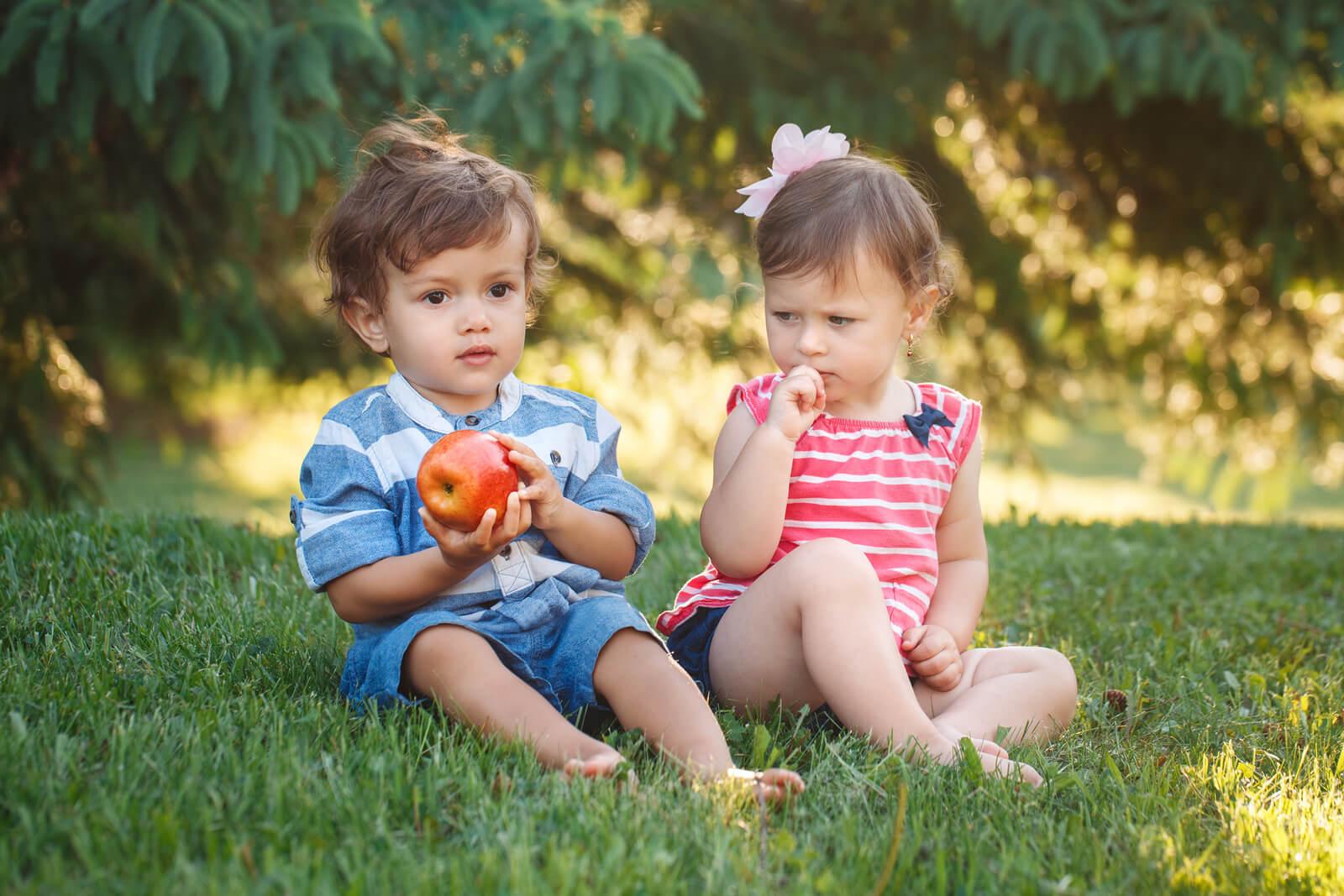 Niña teniendo envidia de su amigo porque tiene una manzana y ella no.