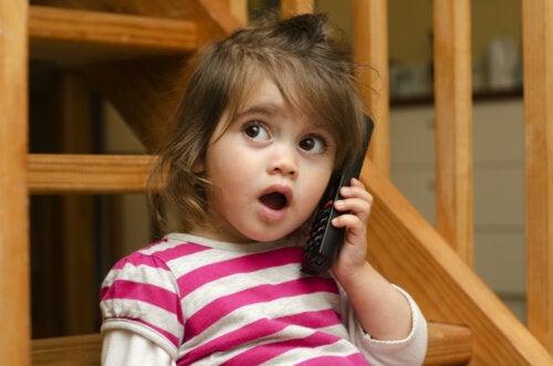 Niña pequeña haciendo que habla por teléfono ya que está en la etapa prelingüística e imita a sus padres.