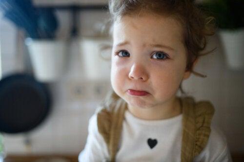 Niña triste durante el confinamiento porque no puede salir a jugar.