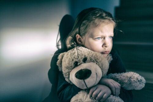 Niña abrazando un oso de peluche como muestra de la depravación afectiva que sufre.