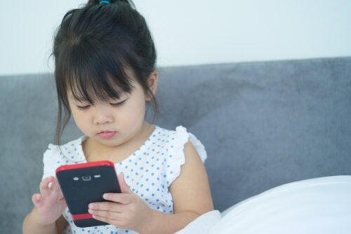 Niña con el teléfono de su padre.