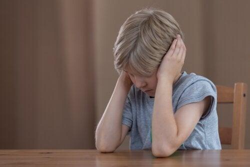 Niño altamente sensible disgustado y tapándose las orejas con las manos para no escuchar.
