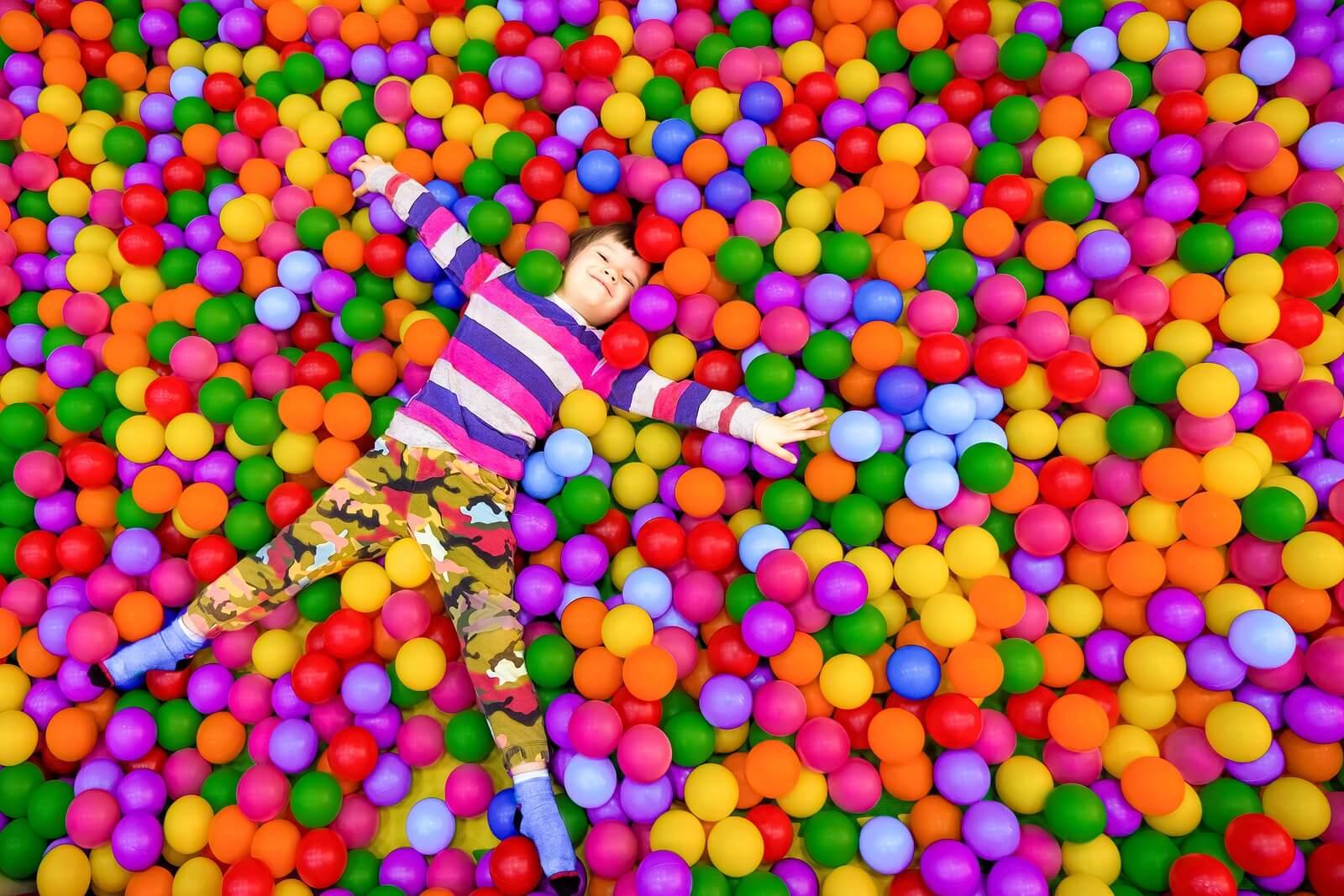 Niño feliz jugando en un parque de bolas.