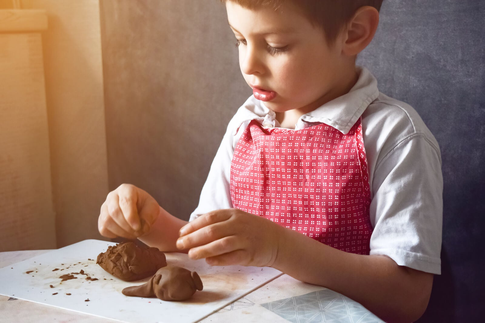 Niño haciendo figuras con arcilla en casa.