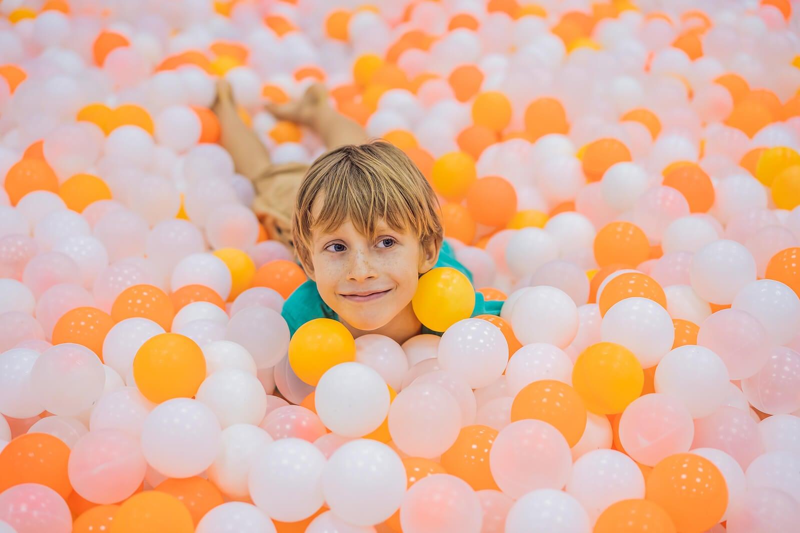 Niño jugando en un parque de bolas.