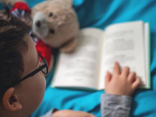 Niño leyendo uno de los libros informativos a su osito de peluche.
