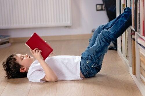 Niño leyendo un libro tumbado en el suelo durante la cuarentena.