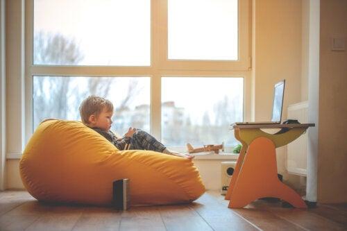 Niño sentando en un puff en su espacio de aprendizaje en casa.