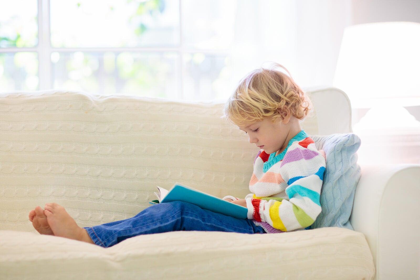 Niño leyendo libros informativos en el sofá de casa.