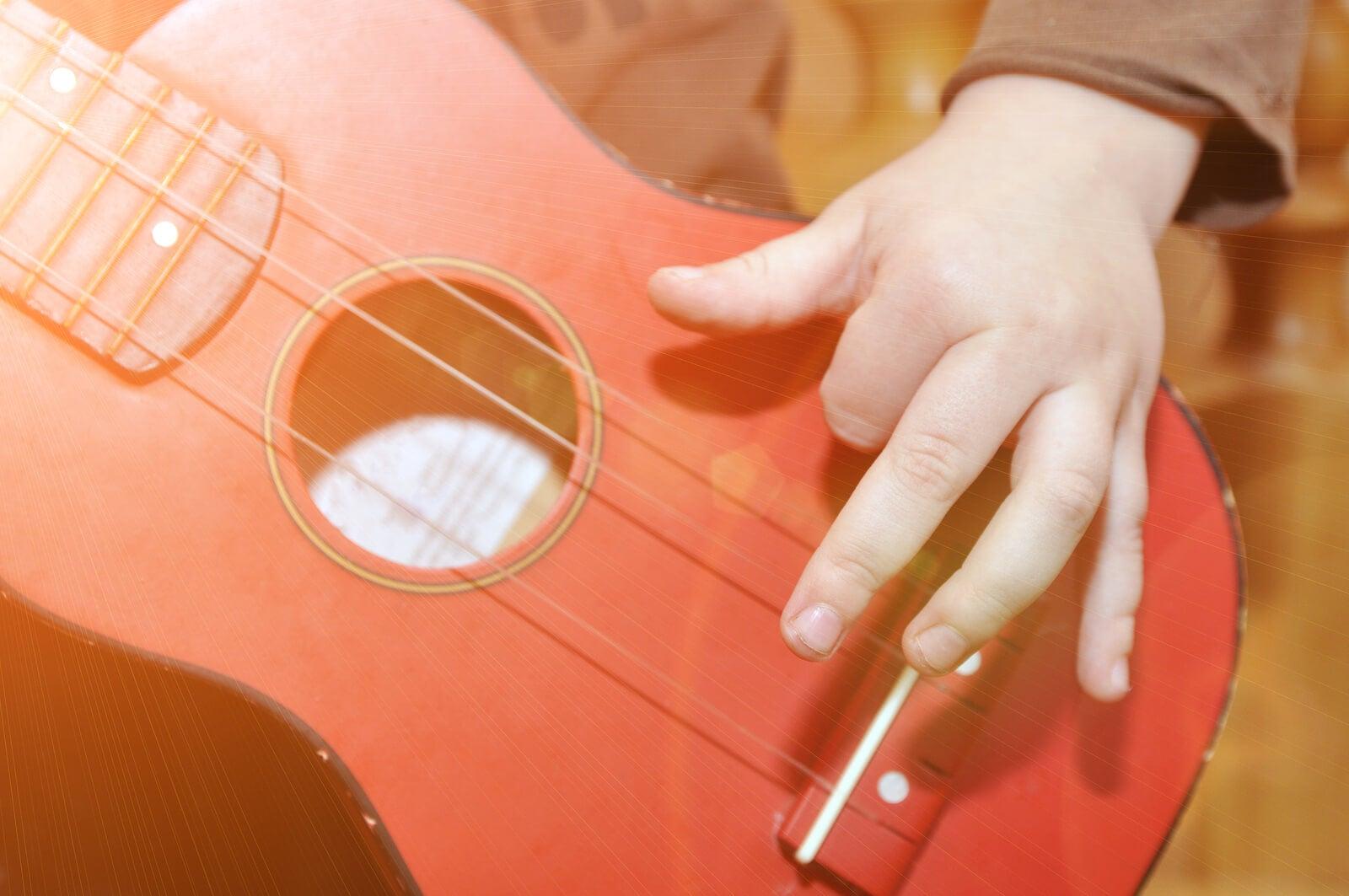 Niño tocando una guitarra de juguete.