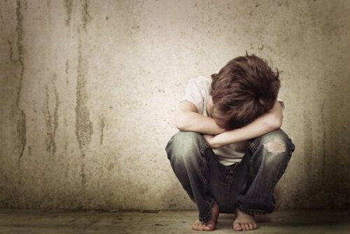 Niño triste sentado en el suelo con mostrando señales de carencia afectiva.