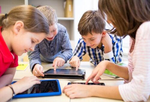 Niños con tablets usando la tecnología en el aula.