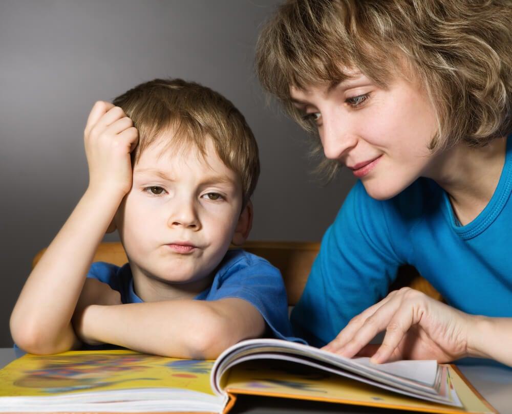 Madre intentando que su hijo aprenda a leer antes de los 6 años.