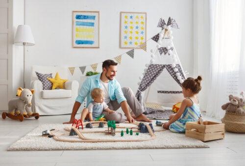 Padre jugando con sus hijos en el salón de casa.