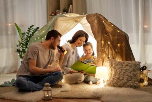 Padres leyendo con su hija en una cabaña construida en el salón de casa.