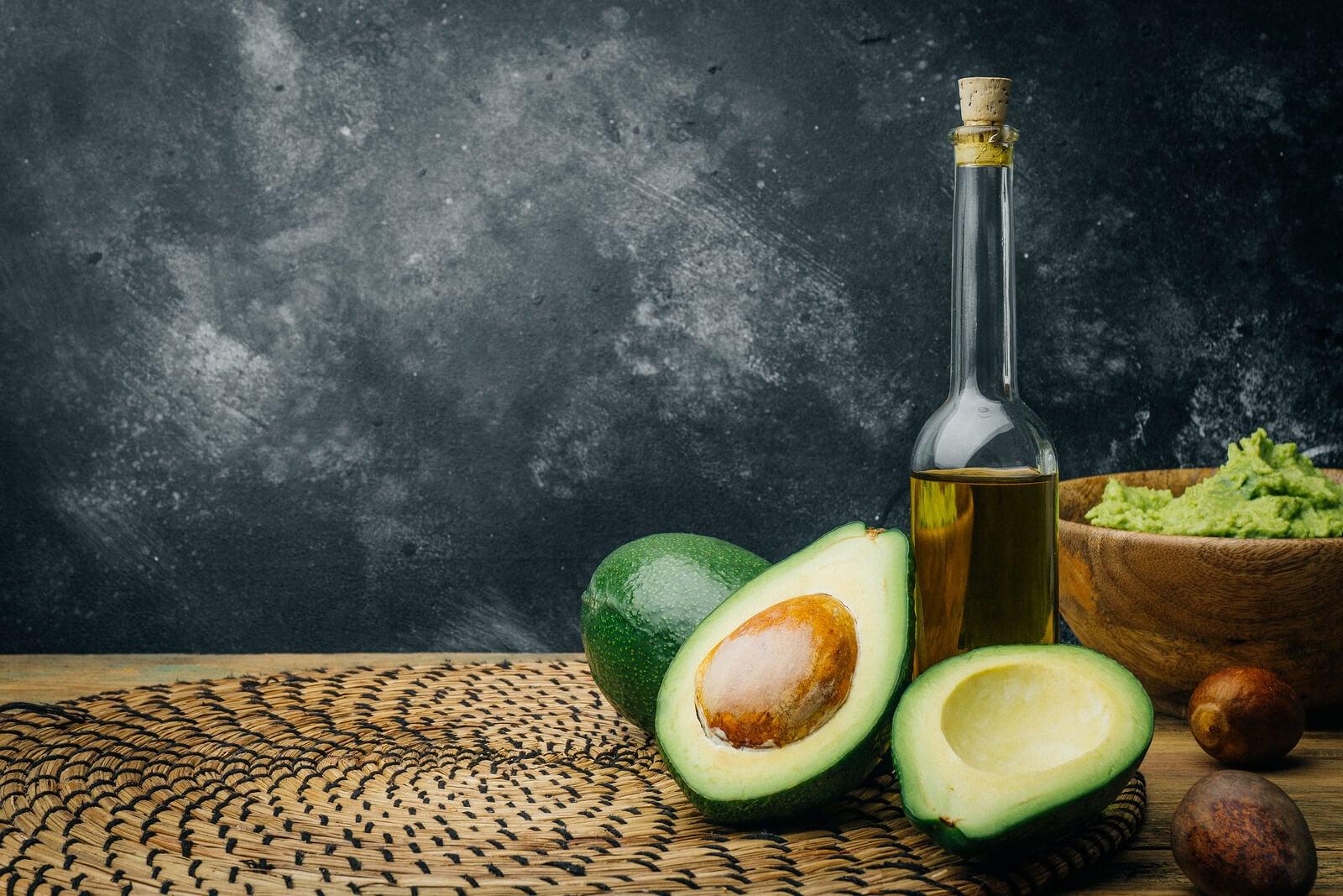 Botella de aceite de oliva y un aguacate, fuentes de grasas saludables.