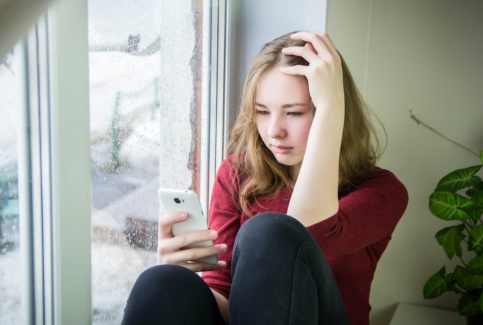 Adolescente con el móvil de la mano sufriendo el síndrome del adolescente normal.