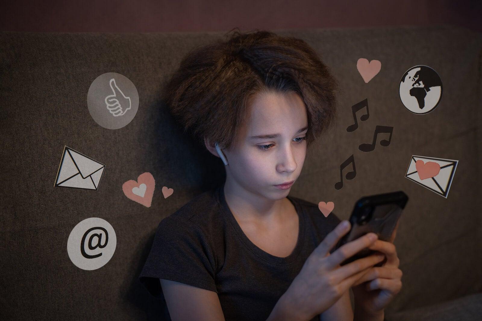 Adolescente usando su primera cuenta en redes sociales en su móvil.