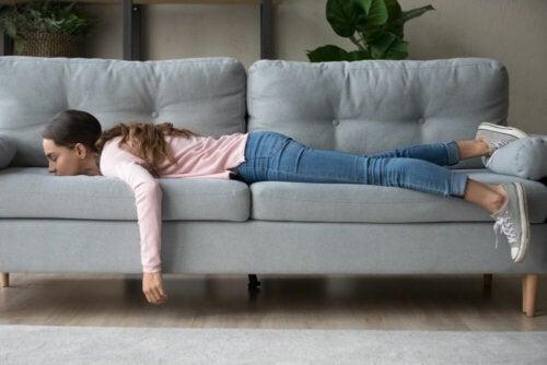 Adolescente tumbada en el sofá sin motivación sufriendo una regresión durante la pandemia.