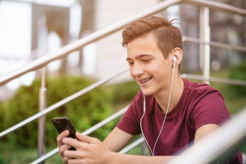 Chico adolescente consultando las redes sociales y sonriendo.