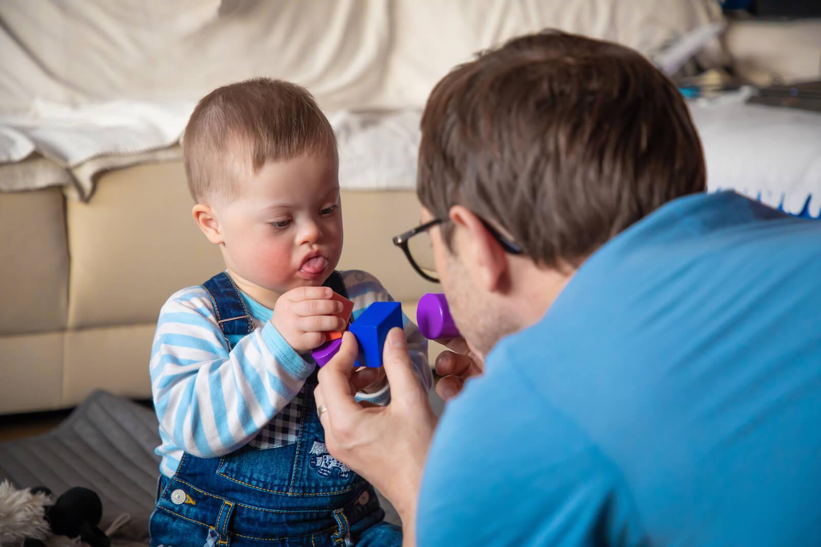 Padre jugando con su hijo con síndrome de Down.