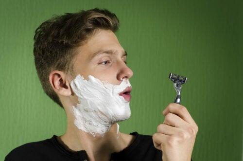 Chico afeitándose la barba.