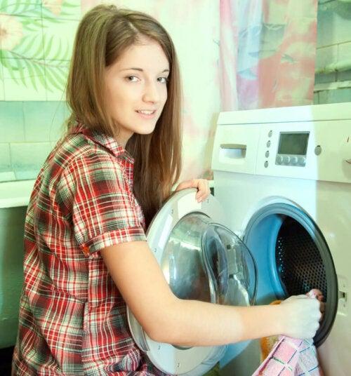 Chica adolescente poniendo la lavadora como parte de sus quehaceres.