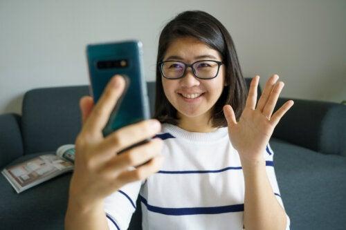 Chica joven haciendo videollamada durante la cuarentena para mantener la distancia social.