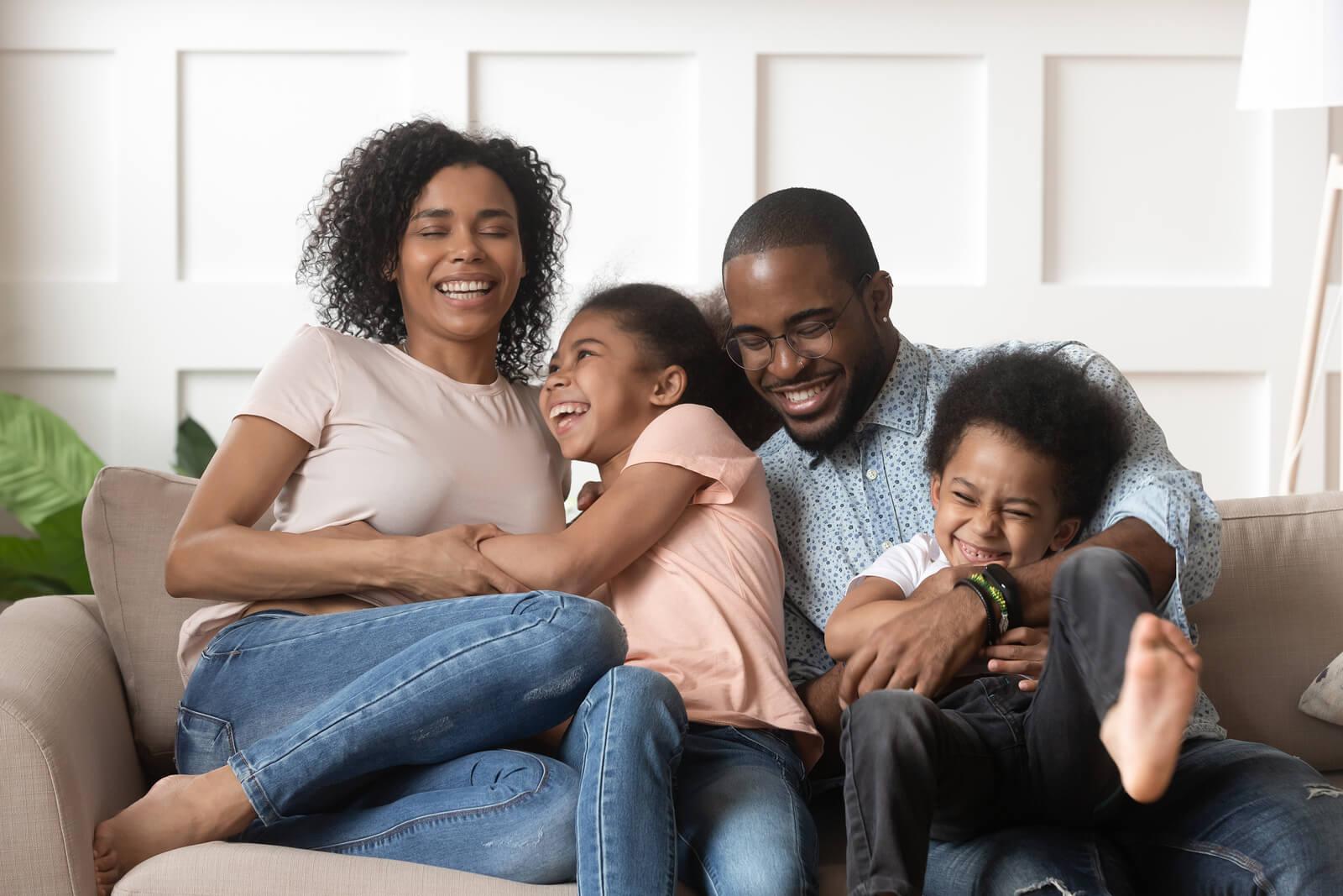 Familia resiliente riéndose en el sofá de casa.