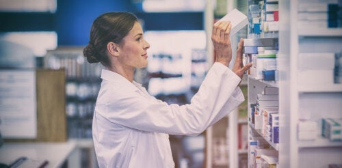 Farmacéutica cogiendo una caja de antibióticos.