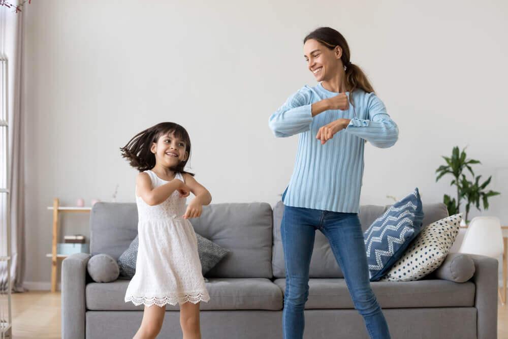 Madre bailando con su hija para tranquilizarla sin utilizar tablet ni móvil.