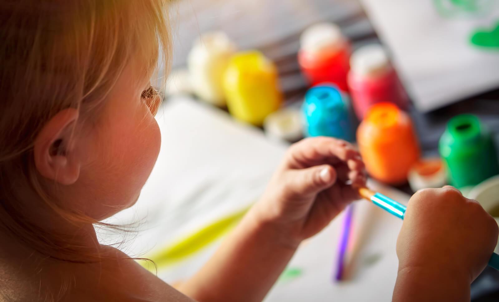 Niña pintando y dibujando para desarrollar su expresión gráfica.